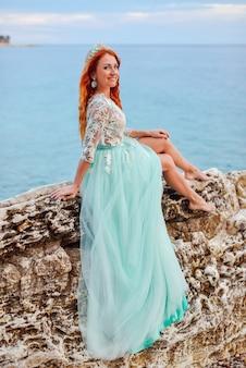 Uma jovem mulher em um vestido de hortelã senta-se em uma grande pedra na costa do mar adriático