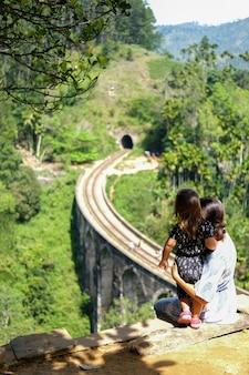 Uma jovem mulher em um vestido leve com a filha olha para a ponte de nove arcos no sri lanka.