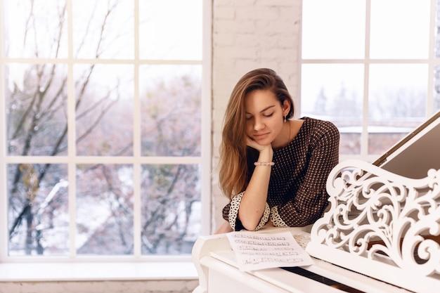 Uma jovem mulher em um vestido marrom perto da janela está inclinada sobre o piano