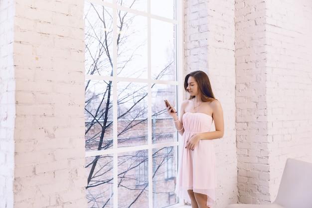 Uma jovem mulher em um vestido rosa está de pé perto da janela com fones de ouvido