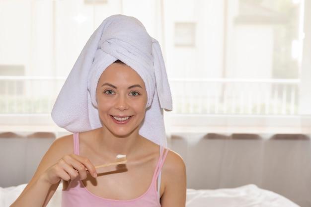 Uma jovem mulher escova os dentes com uma escova de bambu natural