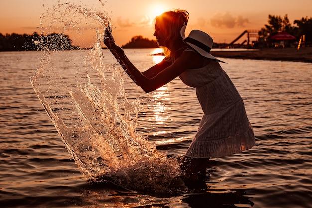 Uma jovem mulher espirra água na foto da silhueta de uma bela loira feliz em um vestido de verão e um vestido ...