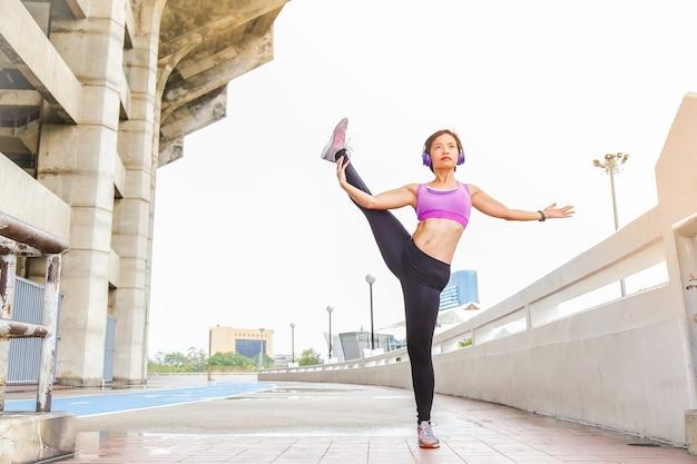 Uma jovem mulher está alongando ou aquecendo seu corpo como uma das poses de ioga