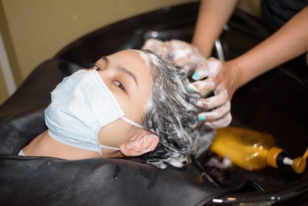 Uma jovem mulher está cortando o cabelo em um salão de cabeleireiro, usando máscara facial para proteção covid-19