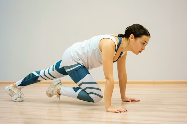 Uma jovem mulher está envolvida em fitness em casa no sportswear. treino e alongamento em casa