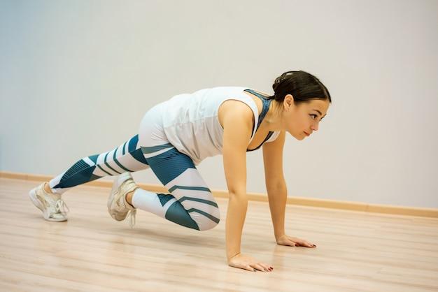 Uma jovem mulher está envolvida em fitness em casa no tapete