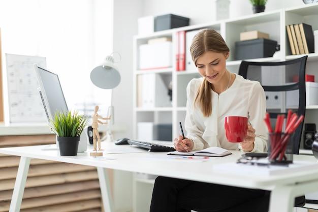 Uma jovem mulher está sentada em uma mesa no escritório, segurando um copo vermelho na mão e escrevendo em um caderno com um lápis.