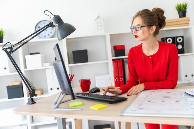 Uma jovem mulher está sentada na mesa do escritório e digitando no teclado.