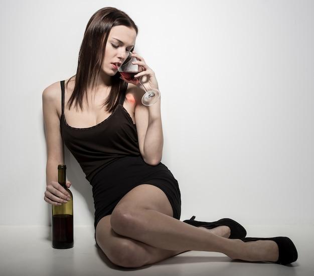 Uma jovem mulher está sentada no chão com um copo de vinho.
