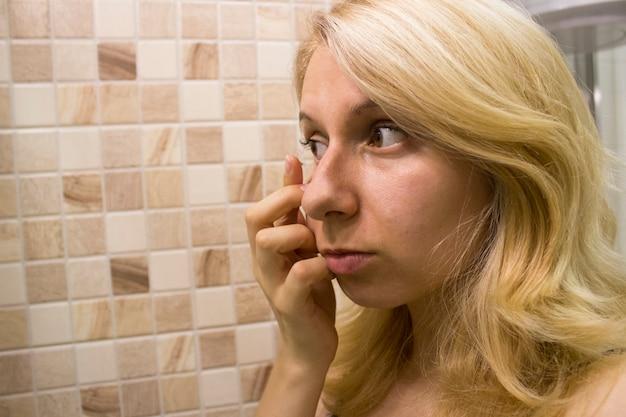 Uma jovem mulher está usando lentes de contato.