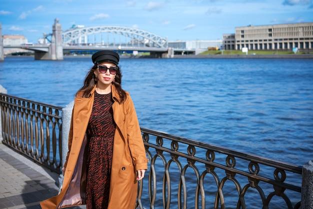 Uma jovem mulher europeia de óculos escuros e um boné preto posa no aterro com um casaco marrom em um sp ...