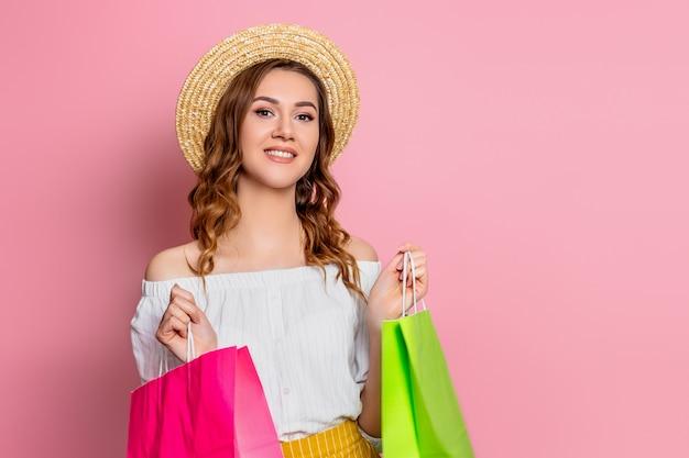 Uma jovem mulher feliz com cabelos ondulados em um chapéu de palha e um vestido vintage sorri com sacos de papel verde e rosa em um conceito de compras on-line de parede rosa