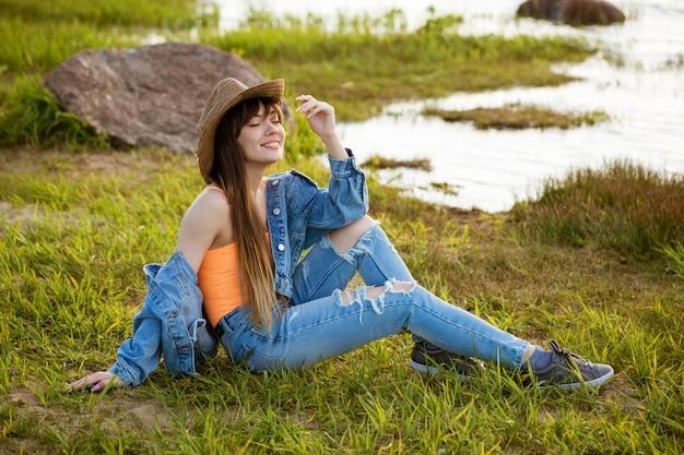 Uma jovem mulher feliz em um terno jeans e um chapéu está sentada na grama sob os raios do sol poente.