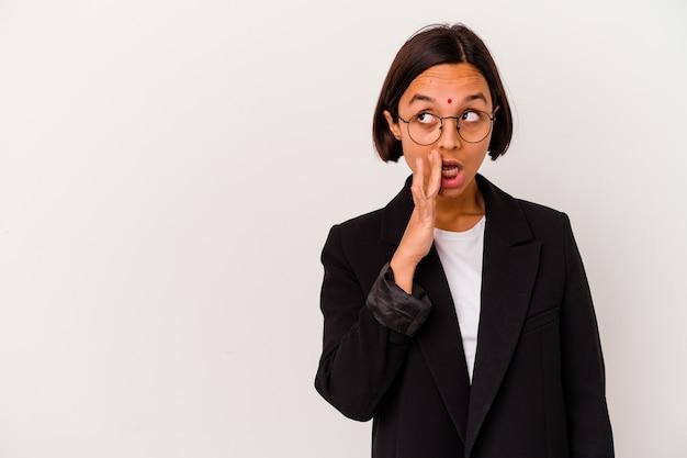 Uma jovem mulher indiana de negócios isolada em uma parede branca está dizendo uma notícia secreta de travagem e olhando para o lado
