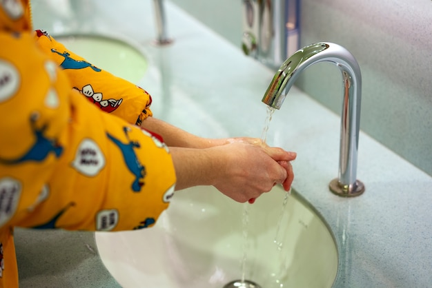 Uma jovem mulher lava as mãos em um banheiro público