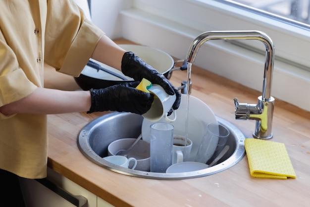 Uma jovem mulher limpa na cozinha, lavando a louça. ela está cansada e não satisfeita com o fato de que precisa fazer isso.