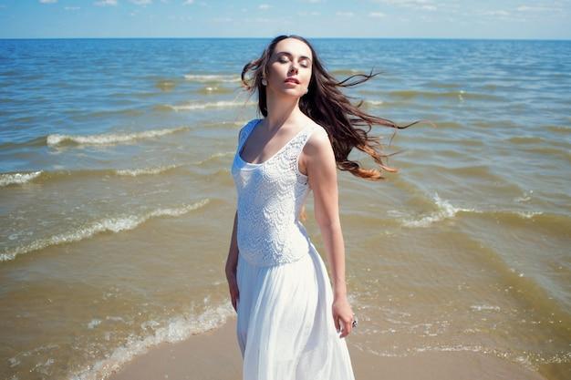 Uma jovem mulher linda em um vestido branco caminha na praia