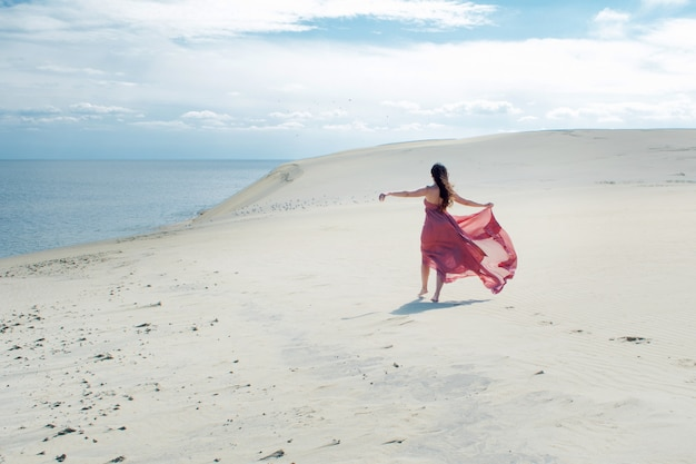 Uma jovem mulher linda em um vestido rosa caminha sobre as dunas de areia