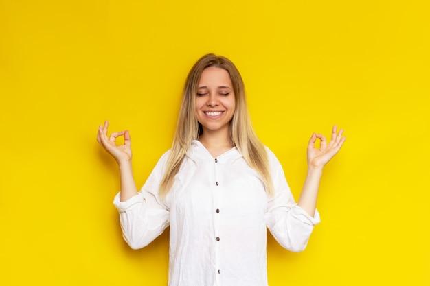 Uma jovem mulher loira atenta, caucasiana, em uma camisa branca mantém as mãos em gesto de mudra com os olhos fechados, isolados na cor amarela. menina calma medita segurando os dedos em um cartaz de ioga