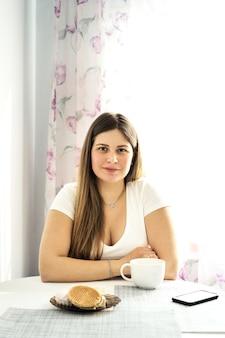 Uma jovem mulher loira de cabelos compridos em uma camiseta branca está bebendo chá f