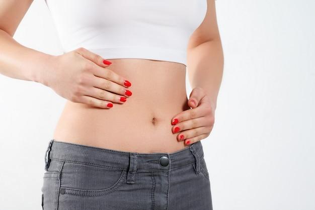 Uma jovem mulher massageia o estômago com as duas mãos. em branco