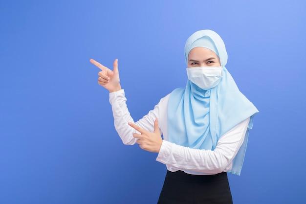 Uma jovem mulher muçulmana com hijab usando uma máscara cirúrgica sobre uma parede azul.