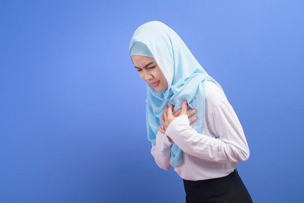 Uma jovem mulher muçulmana usando hijab, sofrendo de dor no peito, parede azul, ataque cardíaco e conceito médico.