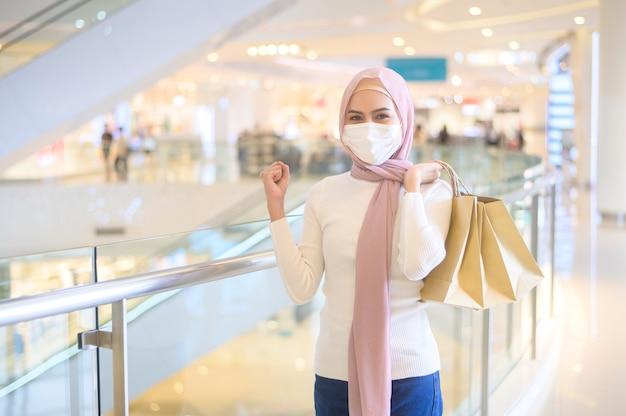 Uma jovem mulher muçulmana usando máscara protetora em shopping center, fazendo compras sob o conceito de pandemia de covid-19.