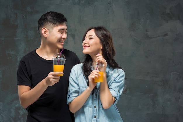 Uma jovem mulher muito asiática com um copo de suco de laranja nas mãos no fundo cinza do estúdio.
