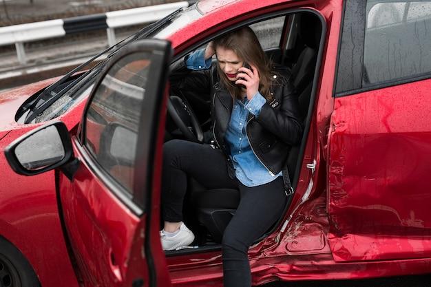 Uma jovem mulher muito assustada no carro liga para um serviço de resgate
