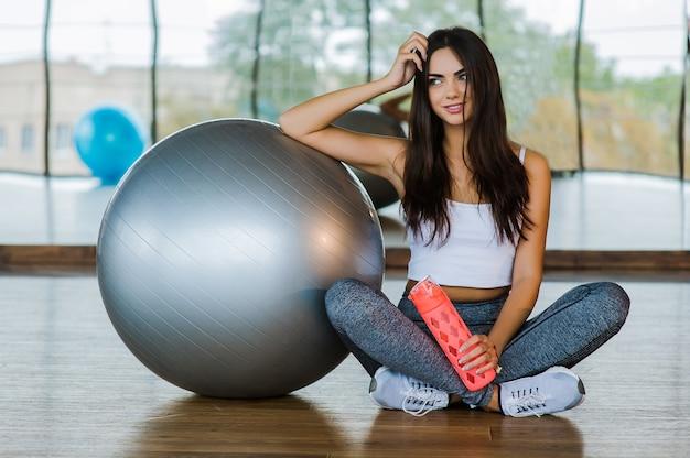 Uma jovem mulher na academia sentada em uma bola de pilates com garrafa