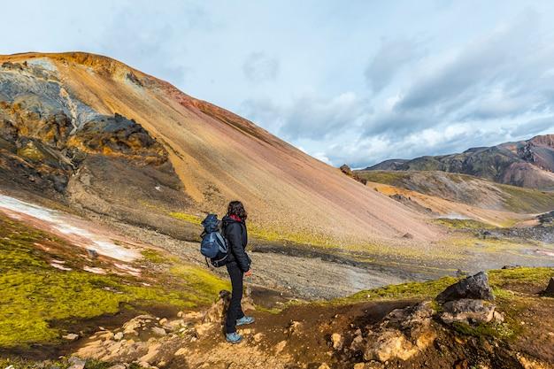 Uma jovem mulher na montanha vermelha da caminhada de 54 km de landmannalaugar, islândia
