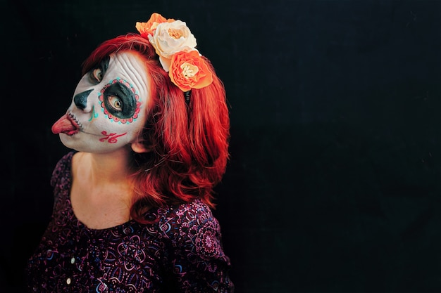 Uma jovem mulher no dia da arte de rosto morto máscara caveira.