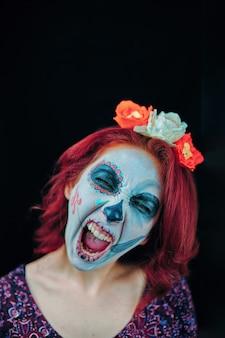 Uma jovem mulher no dia da máscara morta crânio rosto arte