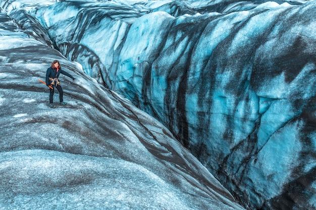 Uma jovem mulher olhando para um dos perigosos buracos de trekking no glaciar svinafellsjokull. islândia