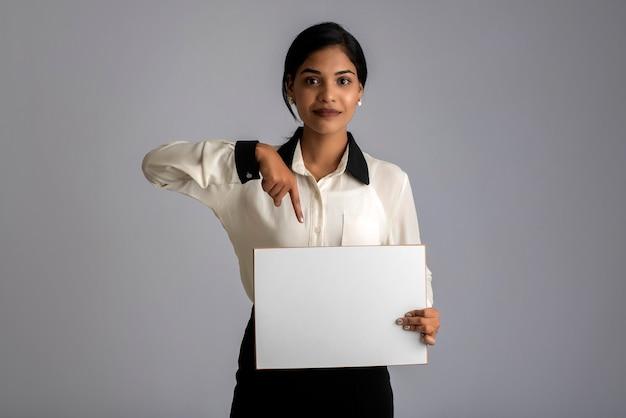 Uma jovem mulher ou mulher de negócios segurando uma placa nas mãos sobre um fundo cinza.