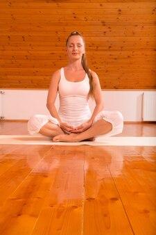 Uma jovem mulher praticando ioga em um estúdio no sótão.