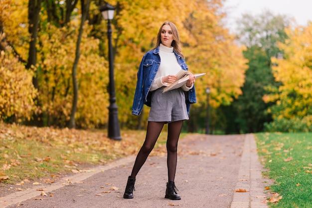 Uma jovem mulher protegendo do vírus corona ao caminhar no parque. fundo de outono.