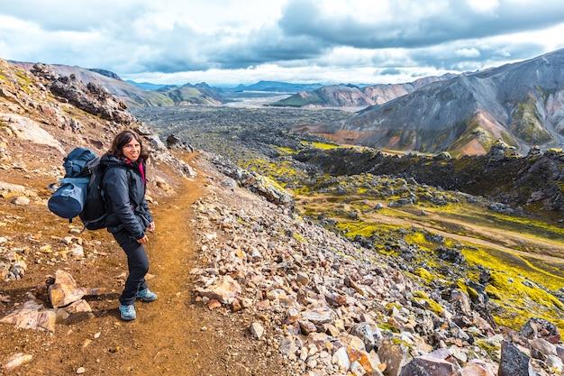Uma jovem mulher que chega ao vale vulcânico de cinzas da caminhada de 54 km de landmannalaugar, islândia