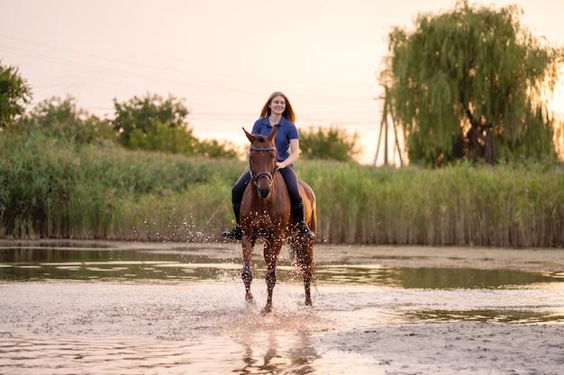Uma jovem mulher que monta um cavalo em um lago raso. um cavalo corre na água ao pôr do sol. cuide e ande com o cavalo. força e beleza