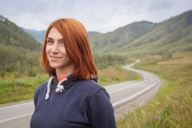 Uma jovem mulher ruiva em um suéter azul sorri