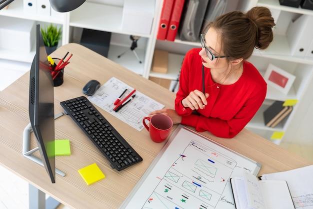Uma jovem mulher se senta em uma mesa no escritório, segura um lápis perto do rosto e olha para o monitor.