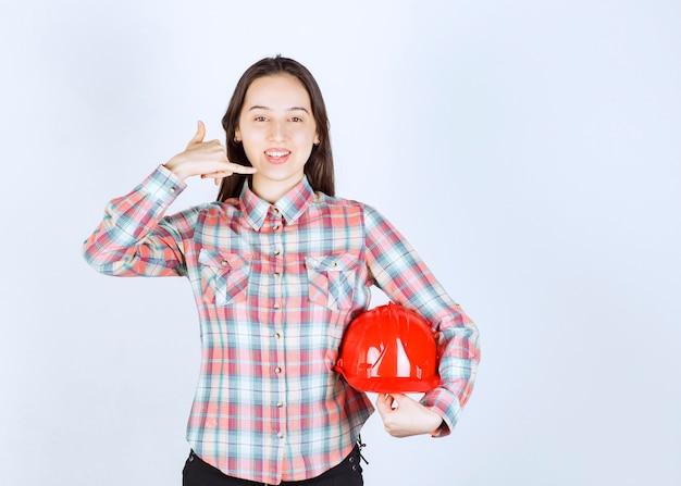 Uma jovem mulher segurando o capacete e fazendo o gesto de telefonema.