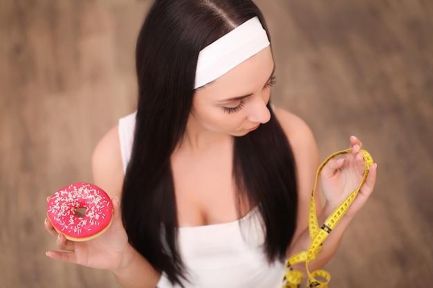 Uma jovem mulher segurando uma rosquinha e uma fita métrica. uma garota fica em um de madeira. a vista do topo. alimentação saudável.