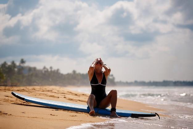 Uma jovem mulher senta-se em uma prancha de surf na areia à beira-mar. descanse após o treino.