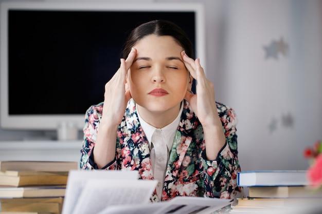 Uma jovem mulher senta-se na frente de uma pilha de papéis