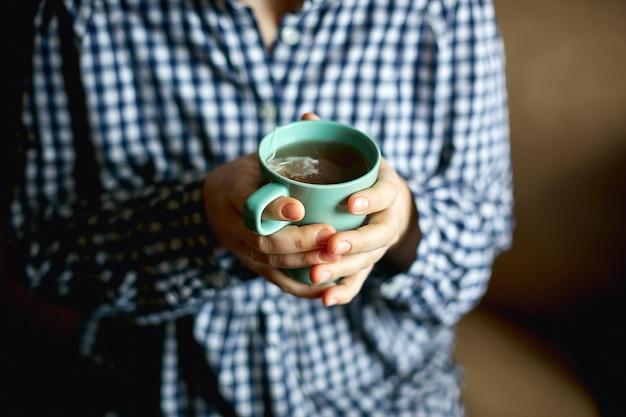 Uma jovem mulher senta-se pela janela e detém uma caneca com chá quente