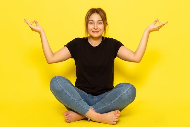 Uma jovem mulher sentada de frente, de camisa preta e calça jeans, meditando com um sorriso amarelo