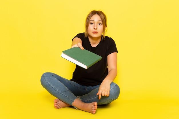 Uma jovem mulher sentada de frente para uma camisa preta e calça jeans segurando um caderno verde sobre amarelo