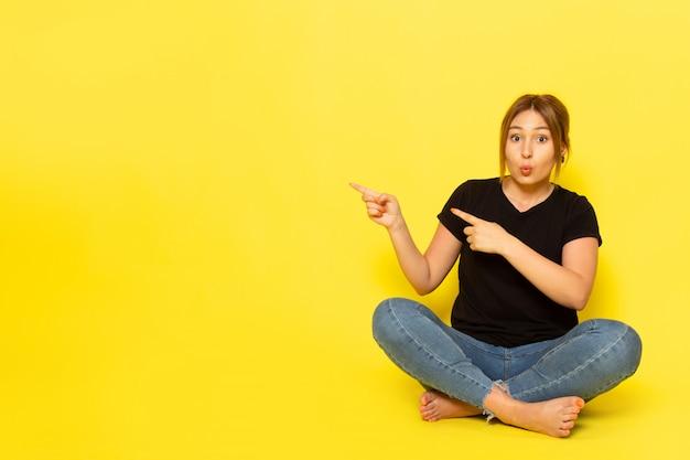 Uma jovem mulher sentada de frente para uma camiseta preta e calça jeans, posando apontando em amarelo